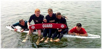 Lifeguards - on surfboards in group photo